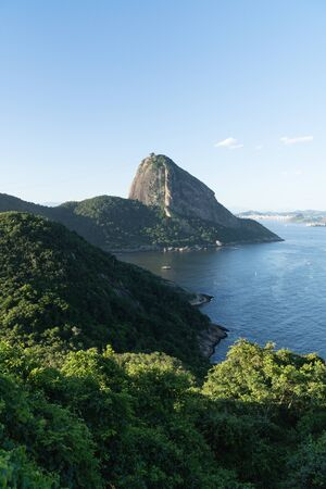 View from the mountain top Forte Duque de Caxias in Leme, Copacabana, overlooking the rock Sugarloaf Mountain in Rio de Janeiro. There is blue sky and sea, green tropical forest, blue sea coastline.