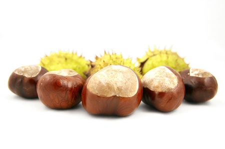 loose skin: Chestnuts with shells behind. Isolated on white. Stock Photo