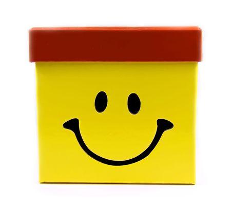 generosidad: Caja de regalo de color amarillo con gran sonrisa y gorra roja.