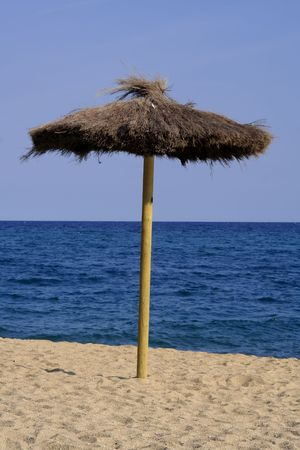 umbrela: Lonely beach umbrella in the blue sky - summer time. Stock Photo