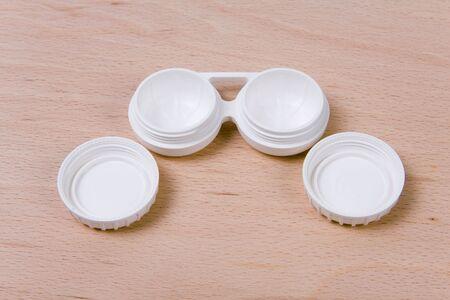 utiles de aseo personal: Conjunto de lente compacto caso. El fondo de madera.  Foto de archivo