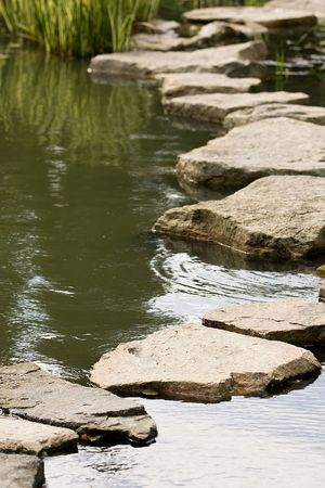 A path from the wet stones, laid through a pond in Japanese to a garden photo
