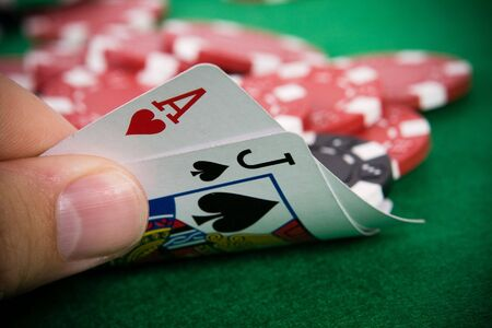 Ace of hearts and black jack with red poker chips in the background. Stock Photo