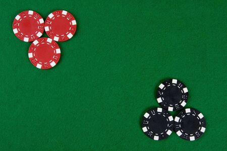 Two kinds of poker chips in two corners of a green poker table. Top view. photo