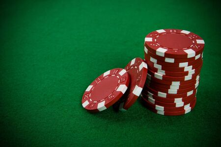 Stack of red poker chips on a green poker table background. photo