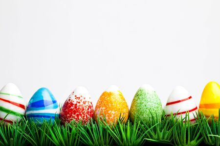 Easter eggs in green grass isolated on white background photo