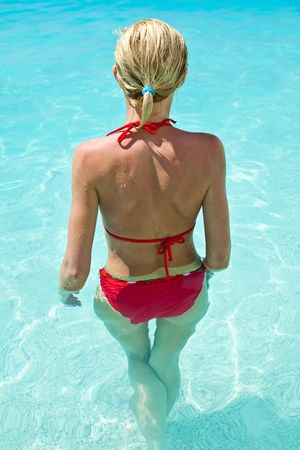 Woman relaxing in blue outdoor swimming waterpool photo