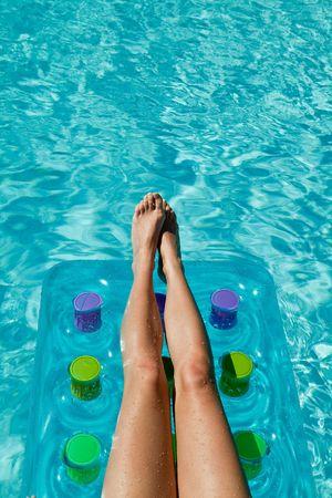 Woman relaxing in waterpool - legs on the mattress photo