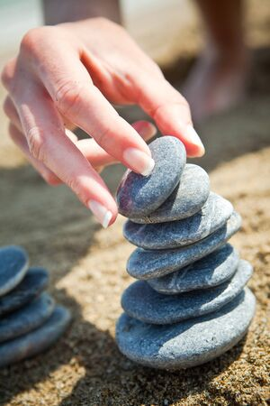 stacking: Woman stacking stones