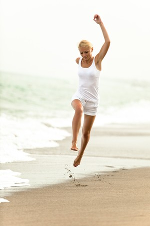 Happy young woman jumping in the beach photo
