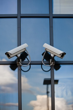 Two security cameras attached on business building with reflections  photo