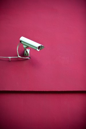 Security camera attached on red building photo