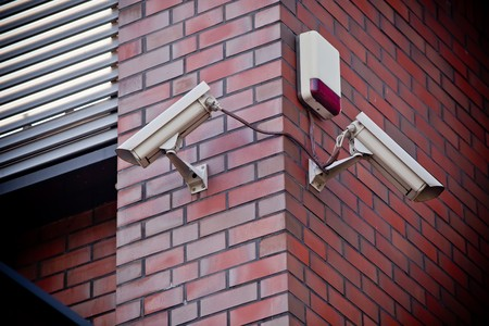 attached: Two security cameras attached on brick wall Stock Photo