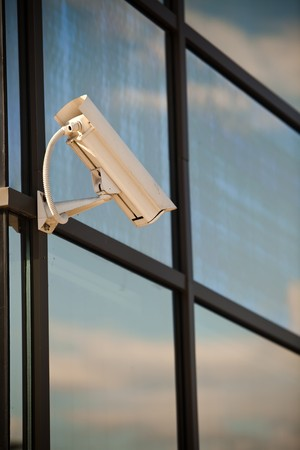 Security camera attached on business building with reflections Stock Photo - 7823630