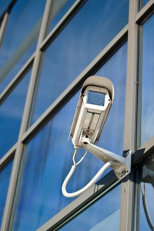 Security camera attached on business building with reflections  photo