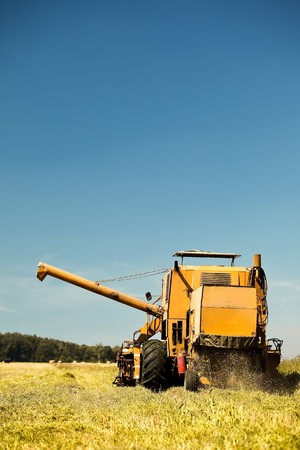 Yellow combine harvester working in a wheat field Stock Photo - 7823572