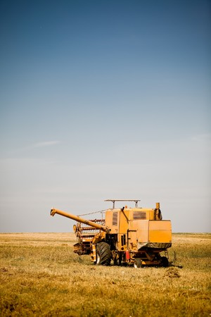 Yellow combine harvester working in a wheat field Stock Photo - 7823328