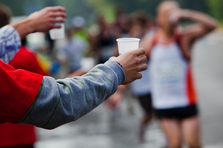 Runner take a water in a marathon race Stock Photo