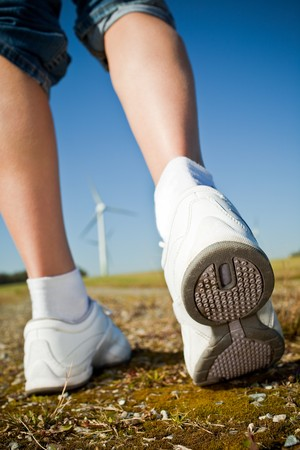 Female hiker walking on a trail - wind turbines in the background Stock Photo