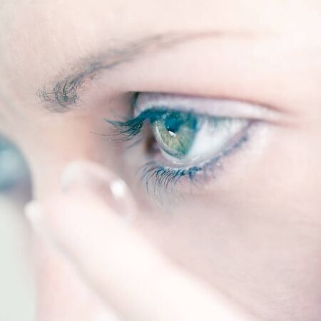 Young woman inserting a contact lens in her eye, close-up