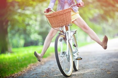 personas: Mujer montando bicicleta con las piernas en el aire