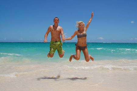 two people jumping on the sea photo