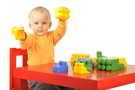 baby is sitting on red chair and playing block toys photo