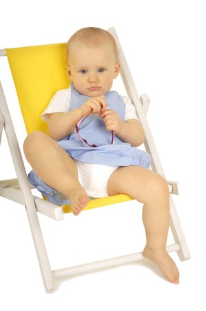 baby with sunglasses sitting on yellow deckchair photo