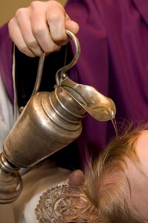 bautismo: sacerdote jefe del niño vierte agua
