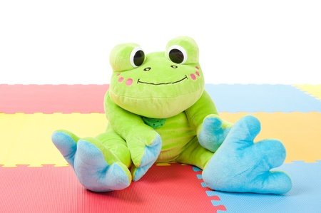 green plush frog sitting on the floor photo