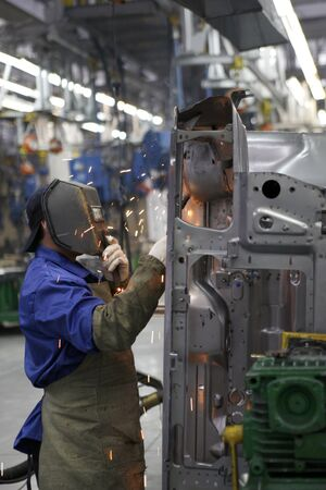 workman in automotive industry welding