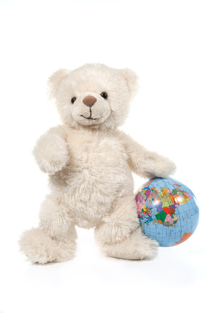 Fluffy white teddy bear with a globe on white Stock Photo