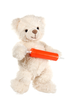 Fluffy white teddy bear with a syringe on white Stock Photo