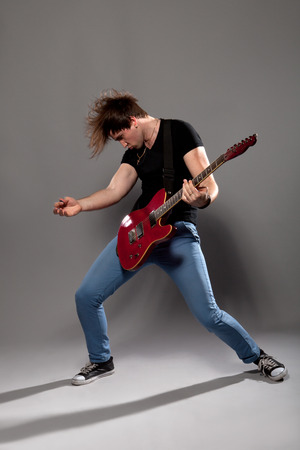Junger Gitarrist spielt auf der E-Gitarre mit hellen Emotionen