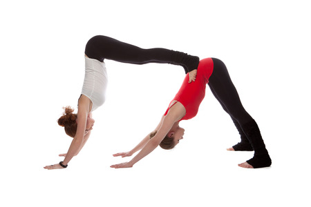 Two girls doing yoga on a white background photo