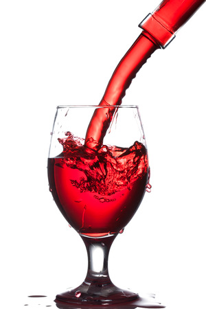 Splash of wine in the cup filling on a white background Stock Photo