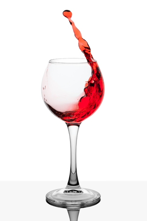 Splash of red wine in the cup filling on a white background Stock Photo