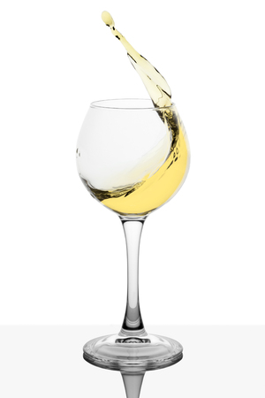Splash of white wine in the cup filling on a white background Stock Photo