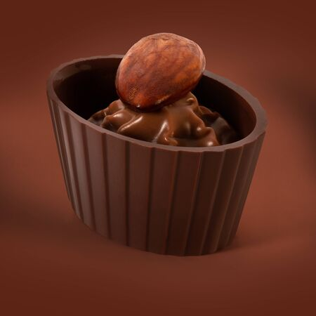 Small chocolate basket with cream and nut on a brown background