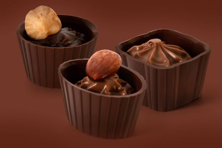 Three small chocolate baskets with cream and nuts on brown background