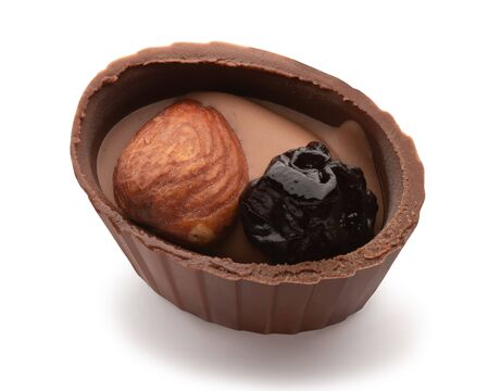 Small chocolate basket with cream, prune and nut on a white background