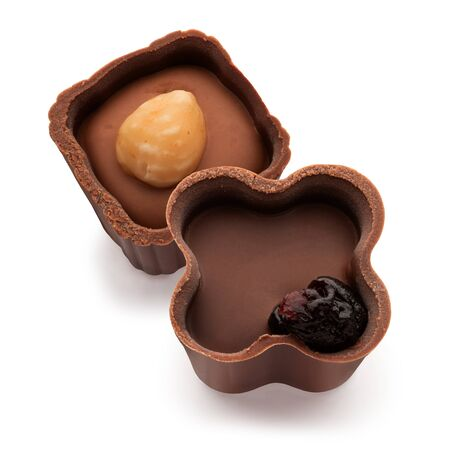 Two small chocolate basket with cream, nut and prunes on a white background