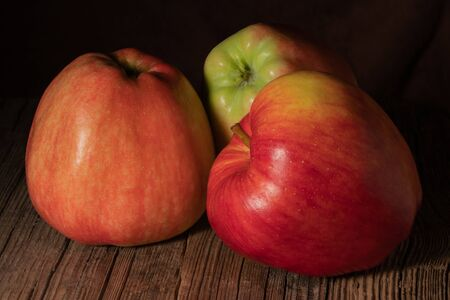 Three textured ripe apple on old wood