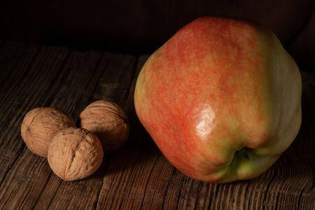 Textured ripe apple and three walnuts on old wood Stock Photo