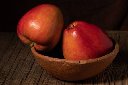 Two textured ripe apple in a clay bowl on old wood