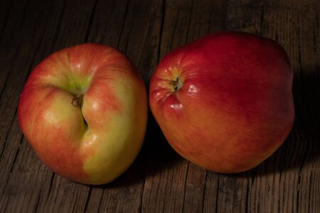 Two textured ripe apple on old wood