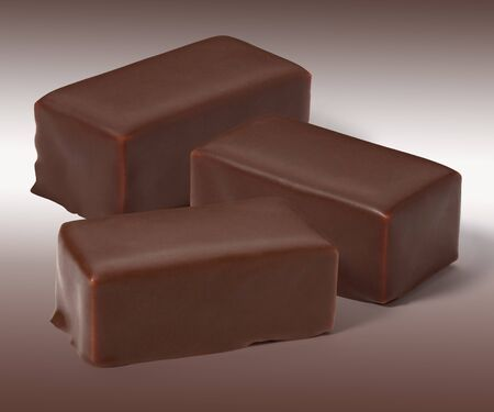 Candies whipped Cream in chocolate on a white brown background