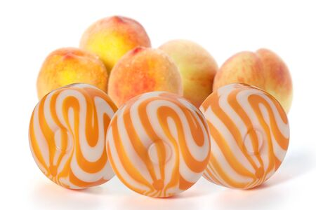 Three round milk caramel with peach flavor and four peaches on a white background