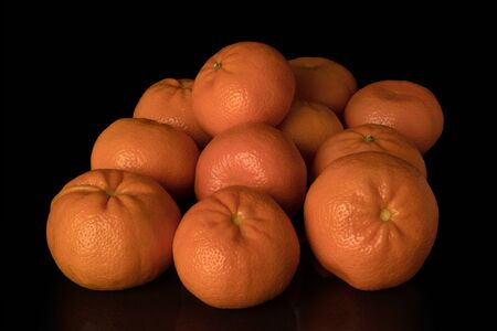 A group of eleven tangerines on a black background