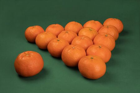 Side view of a billiard pyramid of fifteen tangerines on a green background Stock Photo